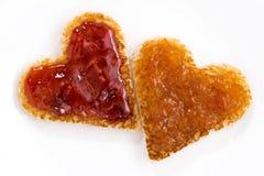 Toasts in heart shape with fruit jam, closeup Stock Photos