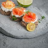 Toasts with lightly salted salmon and cottage cheese cream on a concrete plate. Toasts with lightly salted salmon and cottage cheese cream on concrete plate Stock Images