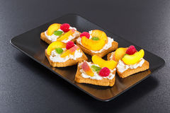 Toasts with mascarpone cheese, raspberry and peach. Decorated with mint leaves on black dish on dark background, view from above, close-up royalty free stock photo