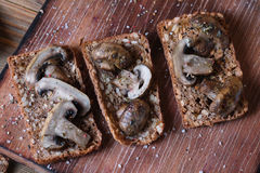 Toasts with mushrooms on wood background. Royalty Free Stock Image