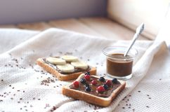 Toasts with peanut butter and berries, bananas on a wood background royalty free stock image
