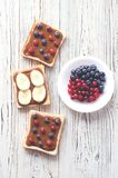 Toasts with peanut butter and berries, bananas on a wooden background stock photography