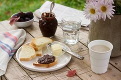 Toasts with plum chocolate jam and cocoa. Breakfast in the garden. Rustic style, selective focus. Royalty Free Stock Photography