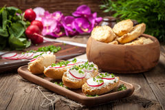 Toasts with radish, chives and cottage cheese on a wooden table. Royalty Free Stock Photography