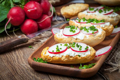 Toasts with radish, chives and cottage cheese on a wooden table. Royalty Free Stock Images
