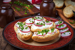 Toasts with radish, chives and cottage cheese on a wooden table. Stock Photos