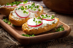 Toasts with radish, chives and cottage cheese on a wooden table. Royalty Free Stock Image