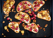 Toasts with ricotta, baked grapes, walnut on black baking Stock Image