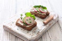 Toasts with rye bread, ricotta ,radish and cucumber Stock Photos