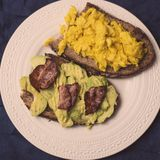 Toasts with scrambled eggs,  avocado and bacon Stock Images
