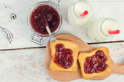 Toasts with strawberry jam and milk. For breakfast on white rusric wooden background. Top view Stock Images