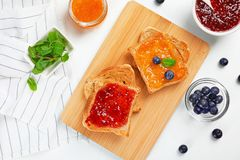 Toasts with sweet jam on light background. Flat lay composition Royalty Free Stock Images