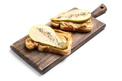 Free Toasts With Pear Slices, Peanut Butter And Chia Seeds On Wooden Board Stock Photo - 143178270