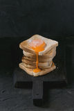 Toasts with yolk over black. Pile of toasts bread with flowing sugared cured yolk on black wooden cutting board over black textured background royalty free stock photography