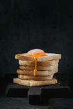 Toasts with yolk over black. Pile of toasts bread with flowing sugared yolk on black wooden cutting board over black textured background stock photo