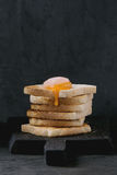 Toasts with yolk over black. Pile of toasts bread with starting flowing sugared cured yolk on black wooden cutting board over black textured background royalty free stock image