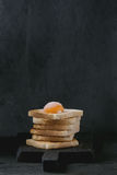 Toasts with yolk over black. Pile of Fresh toasts bread with sugared cured yolk on black wooden cutting board over black textured background stock images