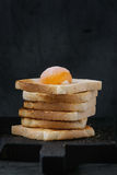 Toasts with yolk over black. Pile of Fresh toasts bread with sugared yolk on black wooden cutting board over black textured background stock image