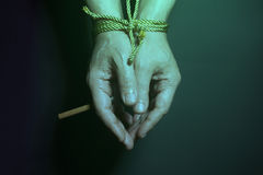 Tobacco addiction. Cigarette on male hands tied with a rope. Royalty Free Stock Image