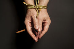 Tobacco addiction. Cigarette on male hands tied with a rope. Stock Images