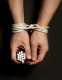 Tobacco addiction. Cigarettes on male hands tied with a rope. Stock Photo