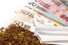 Tobacco, carbon filters, paper against the background of money. Save money when buying tobacco products Stock Photo