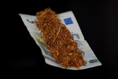 Tobacco and money. Tobacco and rolling money papers stock images