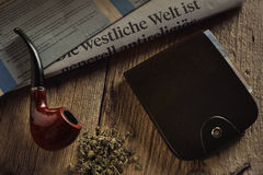 Tobacco pipe with  leather wallet and newspaper Stock Photo