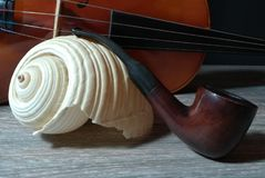 Tobacco pipe, old violin and sea sell. Old violin, smoking pipe and sea sell on black background Stock Photos
