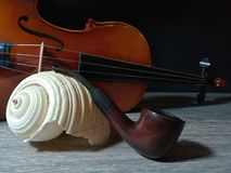 Tobacco pipe, old violin and sea sell. Old violin, smoking pipe and sea sell on black background Royalty Free Stock Image
