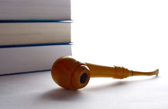 Tobacco pipe and stack of books Stock Image