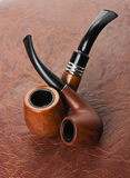 Tobacco pipes on leather background Stock Photo
