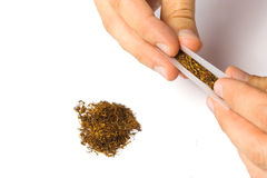 Tobacco rolling. Hand rolling tobacco with more tobacco on the side Royalty Free Stock Photography