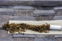 Tobacco. In rolling paper with a slim filter Stock Photo