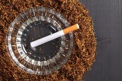 Tobak och cigarett i askfat arkivfoton
