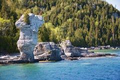 对tobermory视图的小船接近的岩石 图库摄影