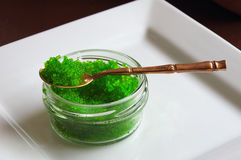 Tobiko green caviar. A glass container of flying fish roe wasabi flavor with a brass bamboo spoon Royalty Free Stock Photos