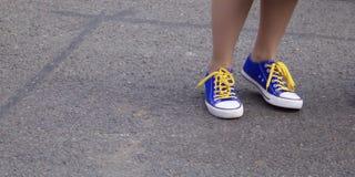 Tobillos de la muchacha que llevan los zapatos azules de los deportes con los cordones amarillos contra el fondo gris del pavimen fotografía de archivo libre de regalías