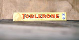 Toblerone -瑞士牛奶巧克力正面图,选择聚焦,黑暗的木背景 库存图片