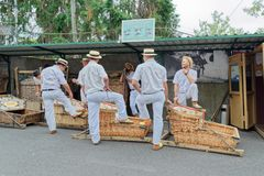 The toboggan drivers with their basket cars waiting for tourists at start point for toboggan run. Monte Funchal, Portugal - 17 September, 2018: The toboggan royalty free stock photo