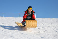 Toboggan jump. Young boy on a wood toboggan going off a snowy jump Royalty Free Stock Photo