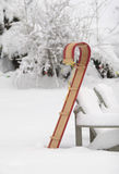 Toboggan in snow. Classic wooden tobagan upright in snowy yard.vertical composition Royalty Free Stock Photo