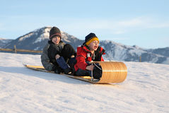 Toboggan for two. Two boys sledding down a hill on a toboggan with excited expressions Stock Image