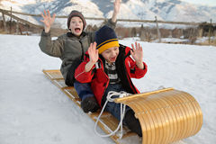 Toboggan for two. Two boys sledding down a hill on a toboggan with excited expressions Royalty Free Stock Images