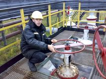 The man in the overalls of Rosneft. The operator turns the handwheel of the valve on the pipeline. Stock Images