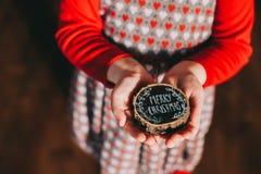 Tocón de madera en las manos de los niños con las palabras, Feliz Navidad Foto de archivo libre de regalías