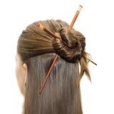 Tocado de la mujer con los palillos asiáticos foto de archivo libre de regalías