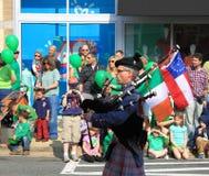Tocador de gaita-de-foles com bandeiras Imagem de Stock Royalty Free