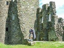 Tocador de gaita de foles escocês tradicional em ruínas do castelo de Kilchurn Imagem de Stock Royalty Free