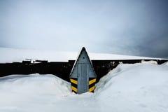 Tocador rodeado por la nieve en invierno cerca de la cerca Foto de archivo